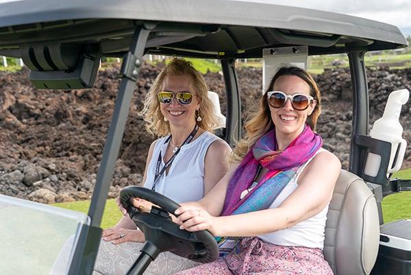 2 women riding in a golf cart