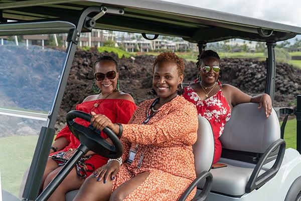 3 women riding in a golf cart